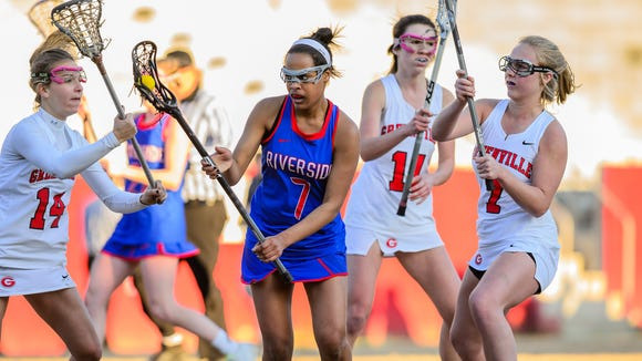 Riverside's Layla Robinson (7) tries to maintain possession amid Greenville defenders during the Warriors' 10-9, double-overtime victory March 13 at Sirrine Stadium.
