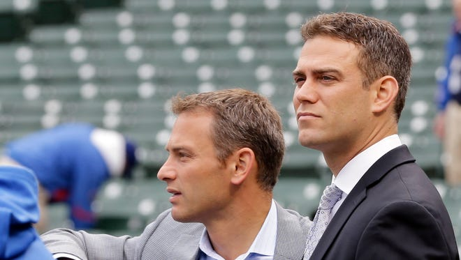 Former Chicago Cubs President of Baseball Operations Theo Epstein, right, and general manager Jed Hoyer watch the team's batting practice before a game. Epstein is stepping down in his role and Hoyer will take over.
