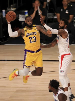 Los Angeles Lakers star LeBron James passes the ball as the Los Angeles Clippers' Marcus Morris Sr. defends during the third quarter at The Arena at ESPN Wide World Of Sports Complex on Thursday in Lake Buena Vista, Fla.