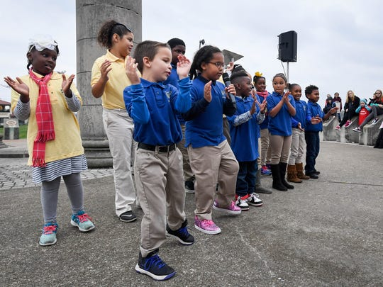 """Children's choir from the Joshua Academy sing """"We Are the World"""" during a gathering at the Four Freedoms Monument before the start of the Children's March on Evansville Sunday, November 12, 2017."""