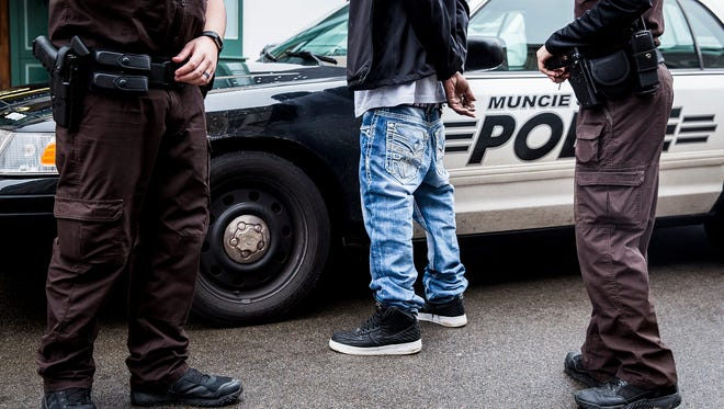 Muncie police arrest a person near one of the city department's vehicles.