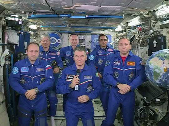In this photo provided by NASA, Italian astronaut Paolo Nespoli, center, and his fellow crew members speak with Pope Francis while aboard the International Space Station on Thursday, Oct. 26, 2017.