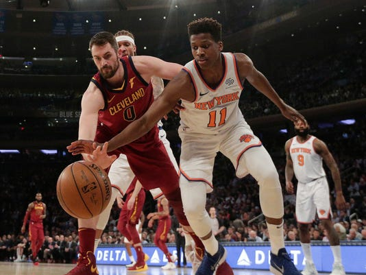 Cleveland Cavaliers center Kevin Love (0) and New York Knicks guard Frank Ntilikina (11) scramble for a rebound during the first quarter of an NBA basketball game, Monday, April 9, 2018, in New York. (AP Photo/Julie Jacobson)