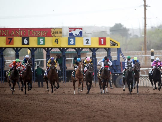 Horses and their jockeys leave the starting gate during