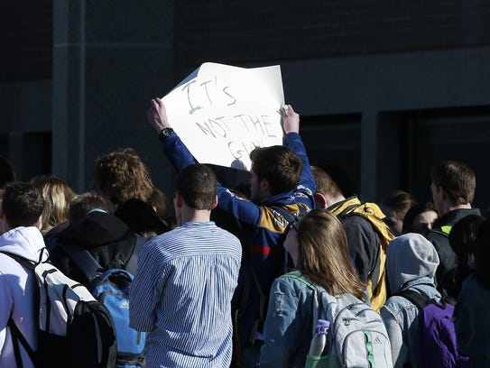 "A student holds up a ""It's not the gun!"" sign during"