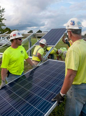 In this 2016 photo, DTE Energy workers install solar panels at the 10-acre O'Shea Playground in Detroit.