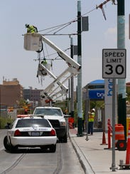 Crews install overhead power lines that will supply