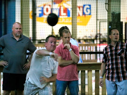 In a photo from June 19, 2015, in Hamtramck, Mich., Jay Rioux tosses a football during a round of Fowling, a sport created by area resident Chris Hutt by combing football and bowling. Hutt believes he can make a buck off the game, opening the 34,000-square-foot Fowling Warehouse inside an industrial park in the Detroit enclave of Hamtramck.
