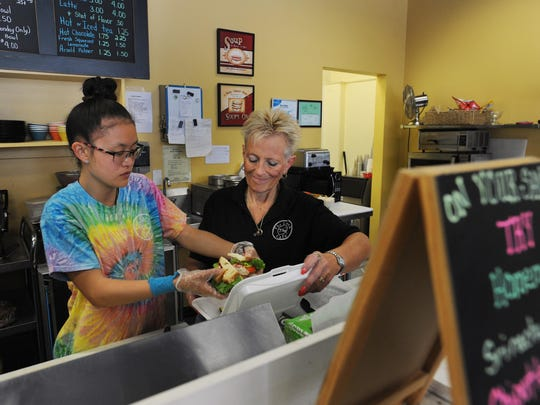 Makenna Calvert, left, and Cinda Coon work at The Lunch Café. Coon is against the plan's closing of streets.