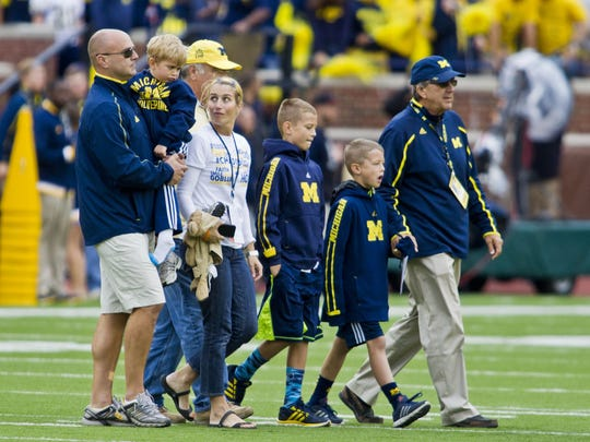 Former Michigan coach Lloyd Carr, far right, leads his grandsons T.J. and Tommy Carr, daughter-in-law Tammi Carr, and son Jason Carr, far left, holding son Chad Carr, onto the Michigan Stadium field for the pregame coin toss, Sept. 12, 2015. Chad Carr, 5, died from an inoperable brain tumor in November.