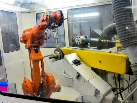 A robot buffs a part used in the medical device industry Tuesday, Sept. 27, at Ultra Machining Co. in Monticello. Robots take over mundane tasks that require great precision and repetition.
