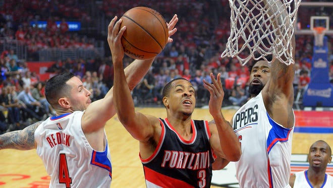 Portland Trail Blazers guard C.J. McCollum, center, shoots as Los Angeles Clippers guard J.J. Redick, left, and center DeAndre Jordan defend during the first half in Game 2 of a first-round NBA basketball playoff series, Wednesday, April 20, 2016, in Los Angeles.