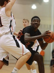 Northeastern's Kobi Nwandu looks around Central York's Sam Saxton  during the boys basketball game at Central York High School Wednesday, December 18, 2013. Central beat Northeastern 65-49.  Kate Penn -- Daily Record/Sunday News