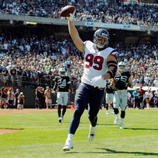 OAKLAND, CA - SEPTEMBER 14:  J.J. Watt #99 of the Houston Texans celebrates after scoring a touchdown against the Oakland Raiders in the first quarter on September 14, 2014 at O.co Coliseum in Oakland, California.  The Texans lead 17-0 in the second quarter.  (Photo by Brian Bahr/Getty Images)
