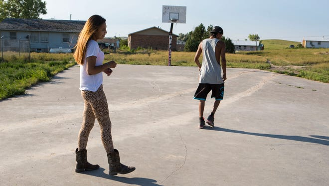 Santana White Dress spends time with her cousin, Jeremy Weston, on a basketball court near childhood home in Oglala on Thursday, July 19, 2018. White Dress, a Miss Basketball finalist for Pine Ridge High, dropped out of college her freshman year due to family concerns.