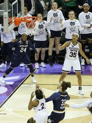 Notre Dame's Arike Ogunbowale (24) hits the game-winner three-pointer as teammate Maureen Butler (third from right) watches from the bench.