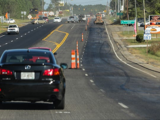 Cars drive on grooved road Thursday on U.S. 76 in Pendleton to get around construction workers laying new asphalt near the S.C. 187 intersection.