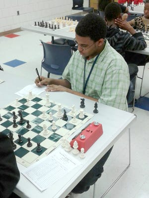 Christopher Thompson, a 9th grader and chess team member at Detroit Collegiate Prep High School at Northwestern, notes his last move during a tournament in February 2016 at the Crowell Recreation Center in northwest Detroit.