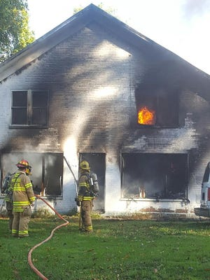 Firefighters work to extinguish a fire on Lucas Perrysville Road in Lucas Sunday, Oct. 23, 2016. The fire remains under investigation.