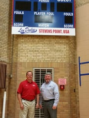 Mike Dudas (left) and Todd Okray (right) of Len Dudas Motors with the new P.J. Jacobs Gymnasium Scoreboard purchased in part by contributions from the company.