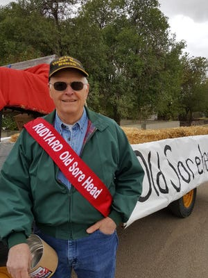 """On a red """"throne,"""" Bob Christenson, the town's new Old Sore Head, led the homecoming parade."""