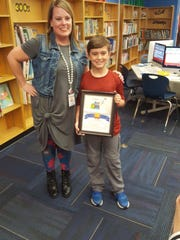 Gifted and Talented coach Meredith Whaley congratulates Luke Akard on his winning drawing.