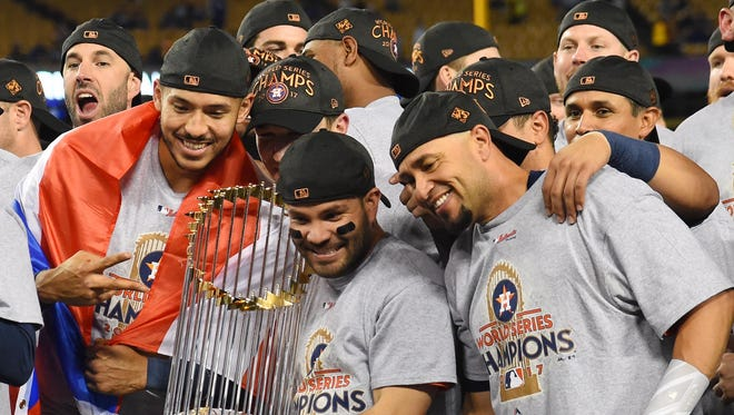 Jose Altuve (center) celebrates with teammates with the Commissioner's Trophy.