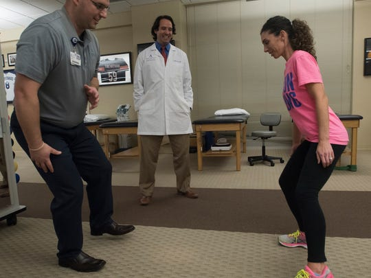 Physical therapist Tyler Opitz, left, works with the