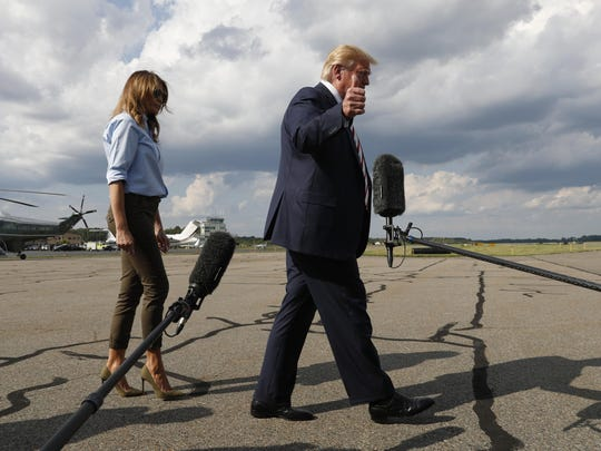 President Donald Trump, with first lady Melania Trump, walks to Airs Force One after speaking to the media before boarding Air Force One in Morristown, N.J., Sunday, Aug. 4, 2019. (AP Photo/Jacquelyn Martin)