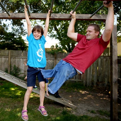 Kacey McCallister plays with his daughter Anna, 9,