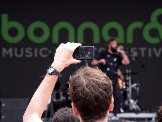 A fan takes a cell phone photo of Mikky Ekko as he performs on the Which Stage at the Bonnaroo Music and Arts Festival in Manchester, Tenn., on June 10, 2018