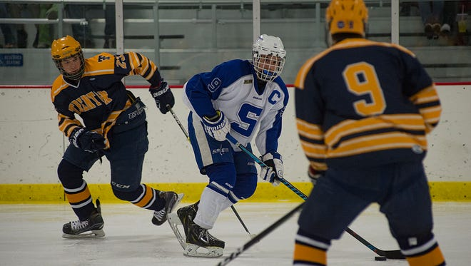 Salem's Matt Schaumburger looks to pass the puck during Friday's season opener. At left is Trenton's Conner Howey (No. 23), while Brandon Morgan of the Trojans waits in the foreground.