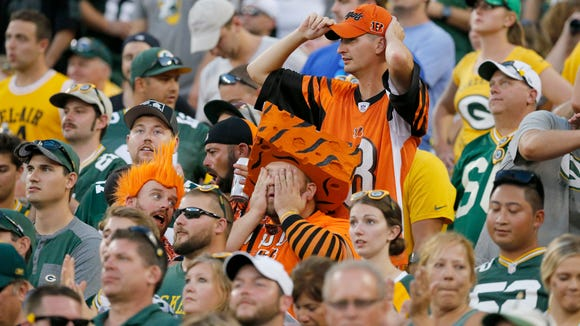 A pair of Bengals fans react as the Bengals fail to score on their possession in overtime of the NFL Week 3 game between the Green Bay Packers and the Cincinnati Bengals at Lambeau Field in Green Bay on Sunday, Sept. 24, 2017. The Bengals were dropped to 0-3 after a 27-24 overtime loss in Green Bay.