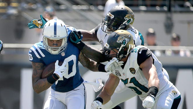 Indianapolis Colts Donte Moncrief makes a catch and runs away from Jacksonville Jaguars Chis Clemons and Paul Posluszny,right, in the second half. The Indianapolis Colts play the Jacksonville Jaguars Sunday, September 21, 2014, afternoon at EverBank Field in Jacksonville FL.