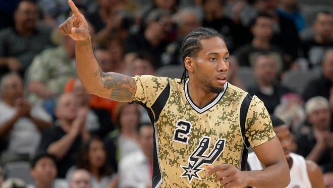 San Antonio Spurs forward Kawhi Leonard celebrates a 3-point basket during the first half of an NBA basketball game against the Miami Heat.