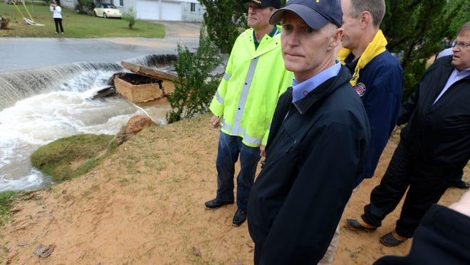 Gov. Rick Scott looks over flood damage in the Cordova Park area with Escambia County officials Wednesday following Tuesday night's torrential rain.