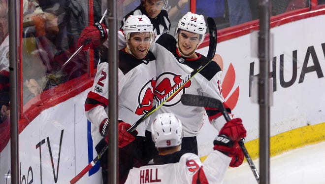 New Jersey Devils defencsman John Moore, left, celebrates his game winning goal against the Ottawa Senators with teammates Nico Hischier, right, and Taylor Hall in overtime in an NHL hockey game, Thursday, Oct. 19, 2017 in Ottawa, Ontario. (Sean Kilpatrick/The Canadian Press via AP)