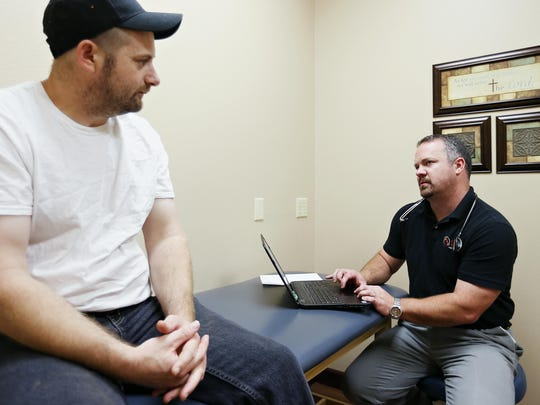 Direct primary care physician Billy Holt examines one of his regular patients, Brian Howe, at Holt's VIP Medical Services practice in Ozark on Oct. 6, 2015.