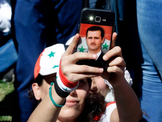 A Syrian woman takes a photo on her phone bearing a