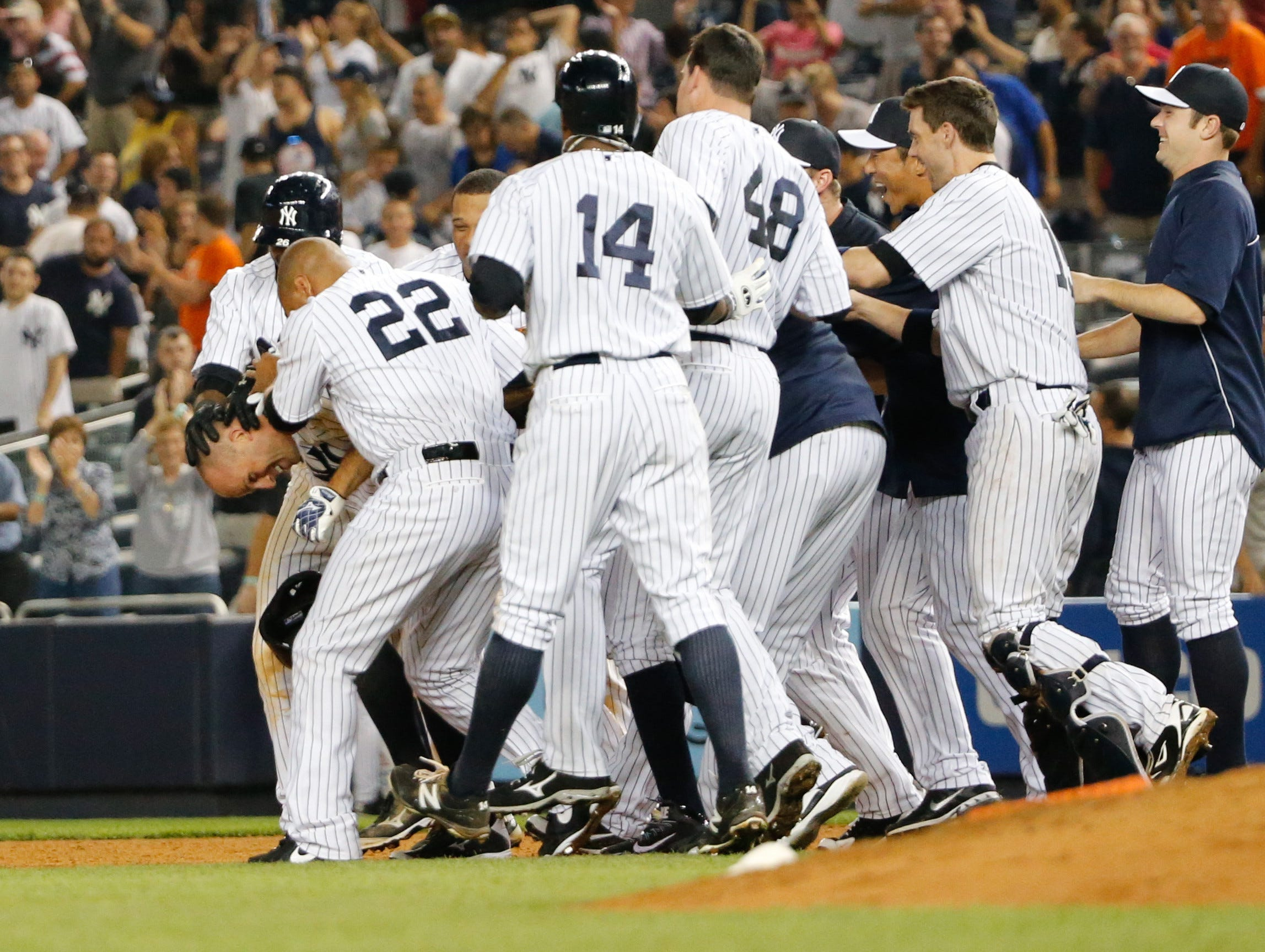 Aug. 9: Teammates mob Yankees center fielder Brett Gardner after his walk-off single in the 10th tenth inning against the Tigers at Yankee Stadium.