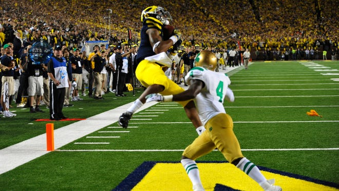 Michigan Wolverines wide receiver Roy Roundtree (12) beats Notre Dame Fighting Irish cornerback Gary Gray (4) to catch the game-winning touchdown on a pass from quarterback Denard Robinson as Michigan defeats Notre Dame 35-31, in the first night game at Michigan Stadium in Ann Arbor on Sept. 10, 2011.
