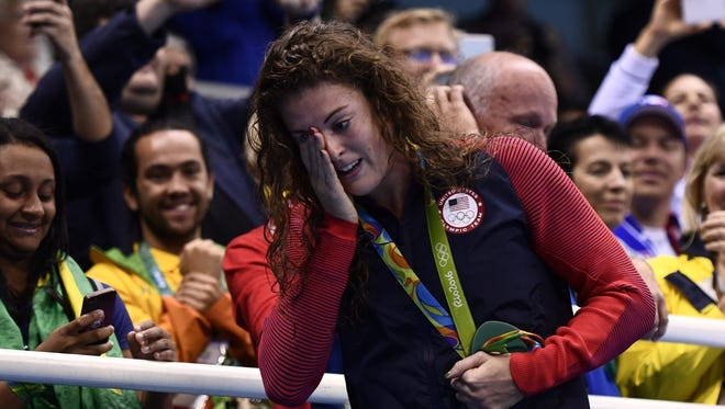 Allison Schmitt wipes away tears during the medal ceremony after Team USA won the women's 800m freestyle relay gold at the Rio 2016 Olympic Games.
