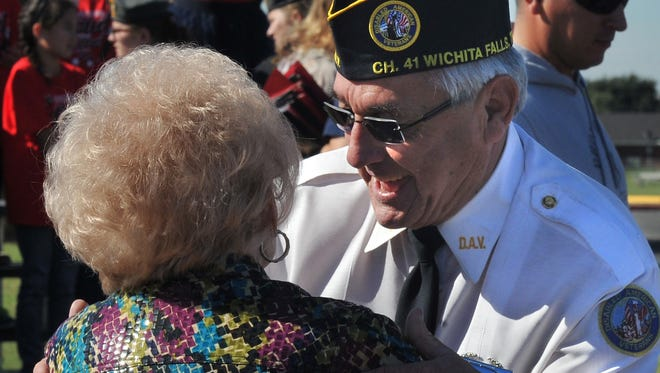 Disabled American Veteran Commander Joel Jimenez received a hug Friday, during the Wichita Falls Independent School District's annual Veterans Day ceremony at Memorial Stadium.
