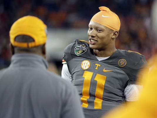 FILE - In this Dec. 30, 2016, file photo, Tennessee quarterback Joshua Dobbs (11) talks on the sideline late in the fourth quarter of the Music City Bowl NCAA college football game against Nebraska in Nashville, Tenn. Regarded as a potential late-round pick or free agent prior to his senior season, the aerospace engineering major now could hear his name called by the second night of the NFL Draft. (AP Photo/Mark Humphrey, File)