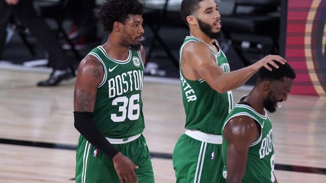 Boston Celtics' Marcus Smart (36), Jayson Tatum, center, and Kemba Walker (8) celebrate as they walk off the court following their NBA conference final playoff basketball game against the Miami Heat on Saturday, Sept. 19, 2020, in Lake Buena Vista, Fla. The Celtics won 117-106.