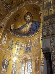 A view of Byzantine mosaics in the nave of the 12th century Norman cathedral in the hillside town of Monreale near Palermo. The hand of the Christ figure is six feet tall.