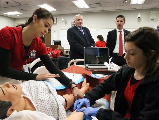 Texas Tech regent Ronnie Hammonds, center, and student