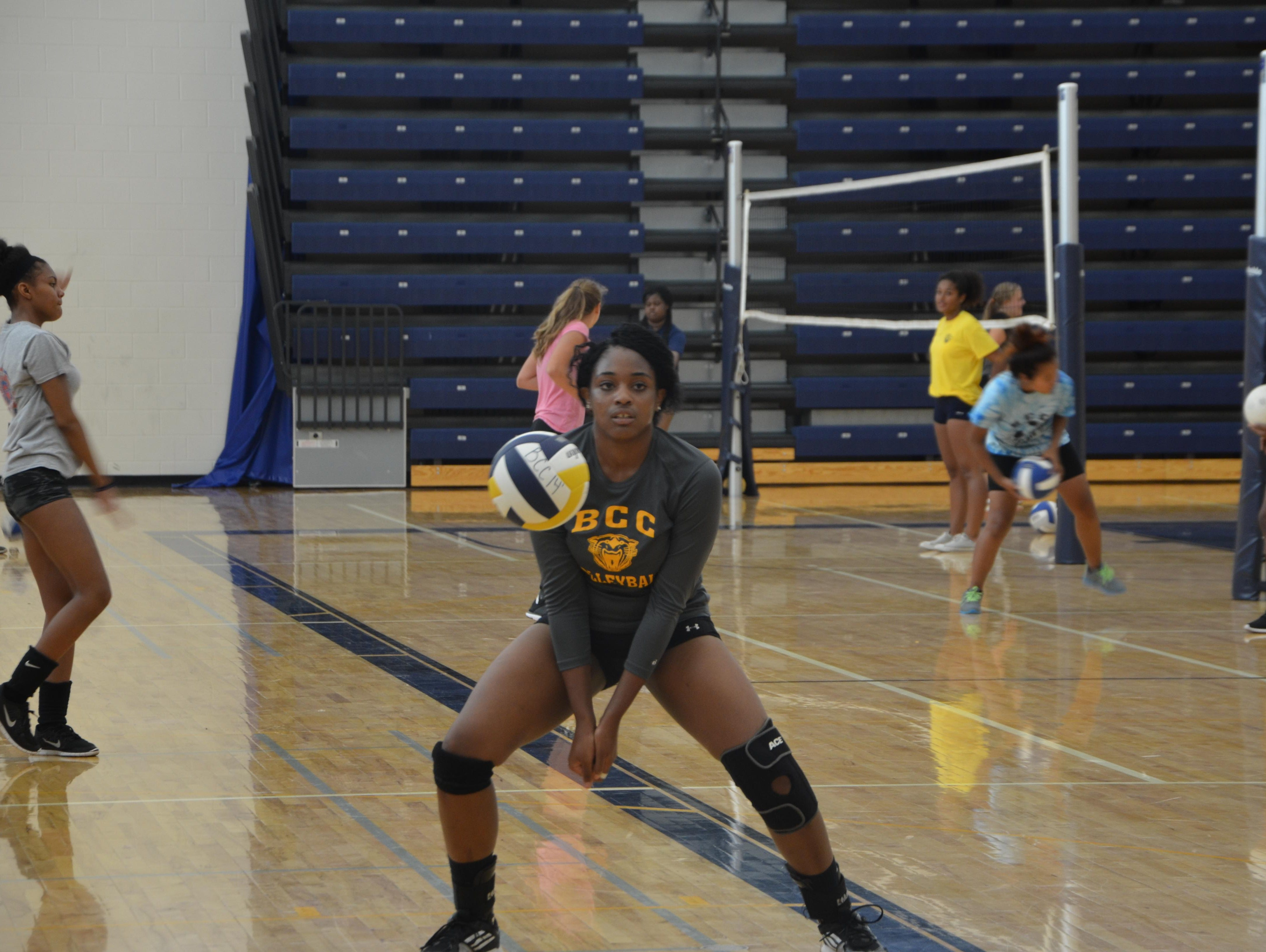 Battle Creek Central's Jamesha Smith digs the ball for a drill during the first volleyball practice of the season on Wednesday.