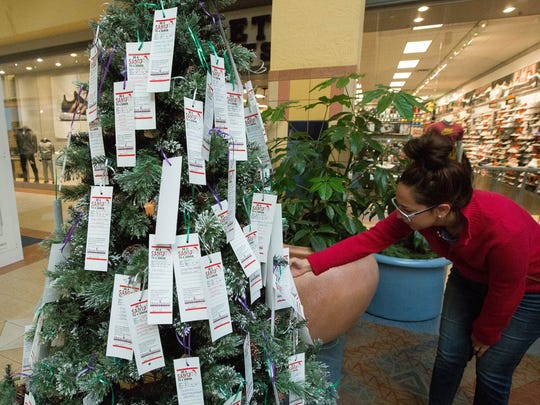 "Adriana Sanchez, looks over the ""Be a Santa to a Senior Tree"" where she was deciding which recipent she would sponser and buy gifts for. Tuesday Nov. 21, 2017."