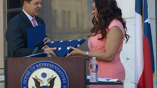 U.S. Rep. Joey Arrington, left, Tuesday hands Angela Underwood Jacobs a U.S. flag on that was flown at United States Capital in honor of her brother, Patrick Underwood, a federal Protective Security Officer who was gunned down in May in California.